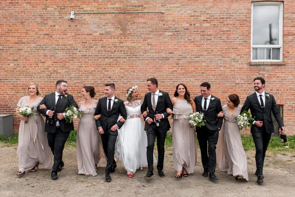 Large wedding party poses in front of a brick wall in Edmonton Alberta