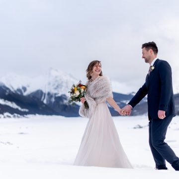 Winter bride and groom walk across snow at Medicine Lake in Jasper National Park on their wedding day