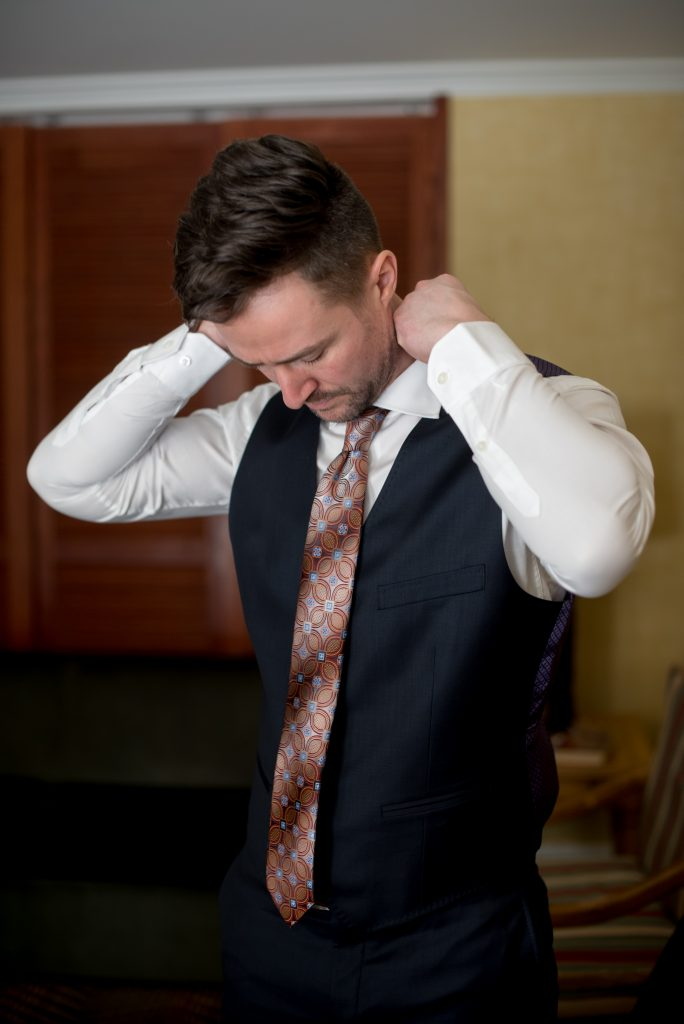 Groom adjusts his collar and tie