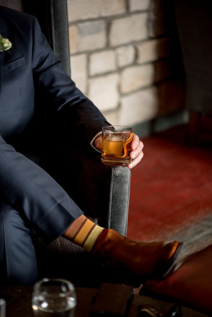 Groom enjoys an Old Fashioned on his wedding day at the bar at the Fairmont Jasper Park Lodge