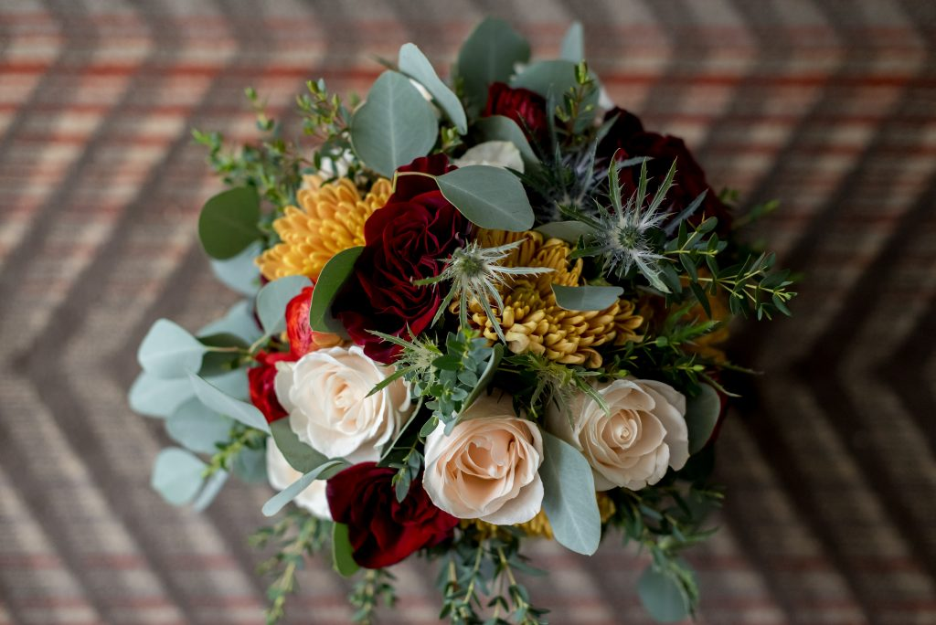 Winter bridal bouquet designed by the Fairmont Jasper Park Lodge filled with bold yellow and crimson hues