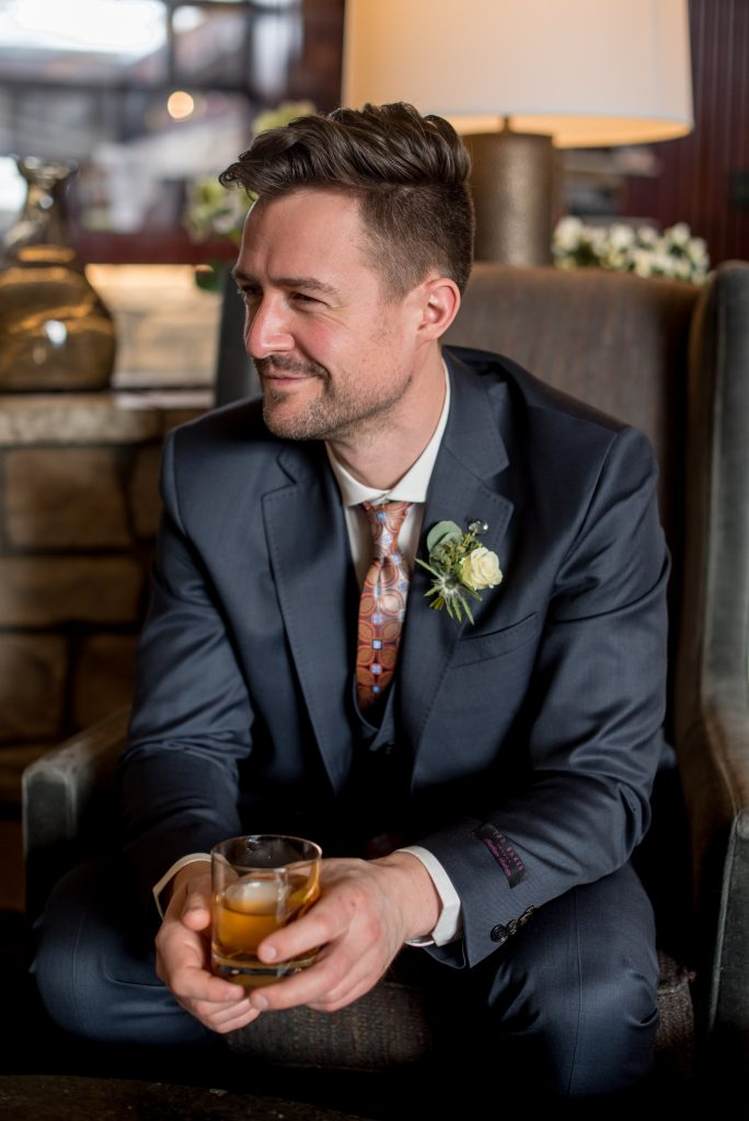 Sophisticated groom in a navy suit enjoys an Old Fashioned at the cocktail bar at the Fairmont Jasper Park Lodge