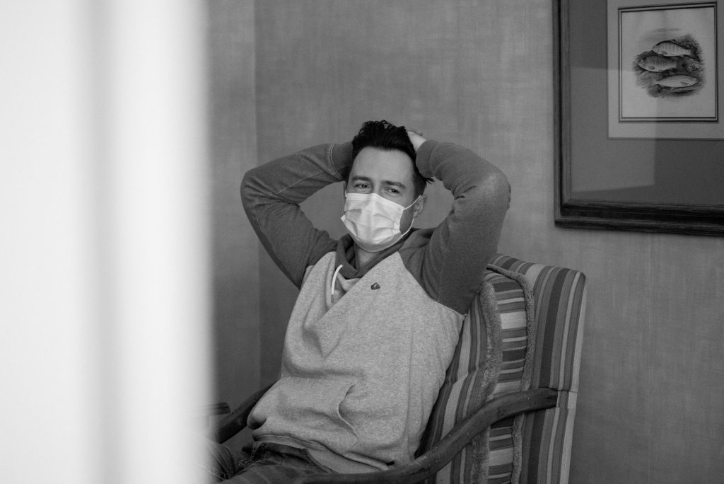 Groom wearing a face mask sits back and relaxes in his room at the Fairmont Jasper Park Lodge on his wedding day