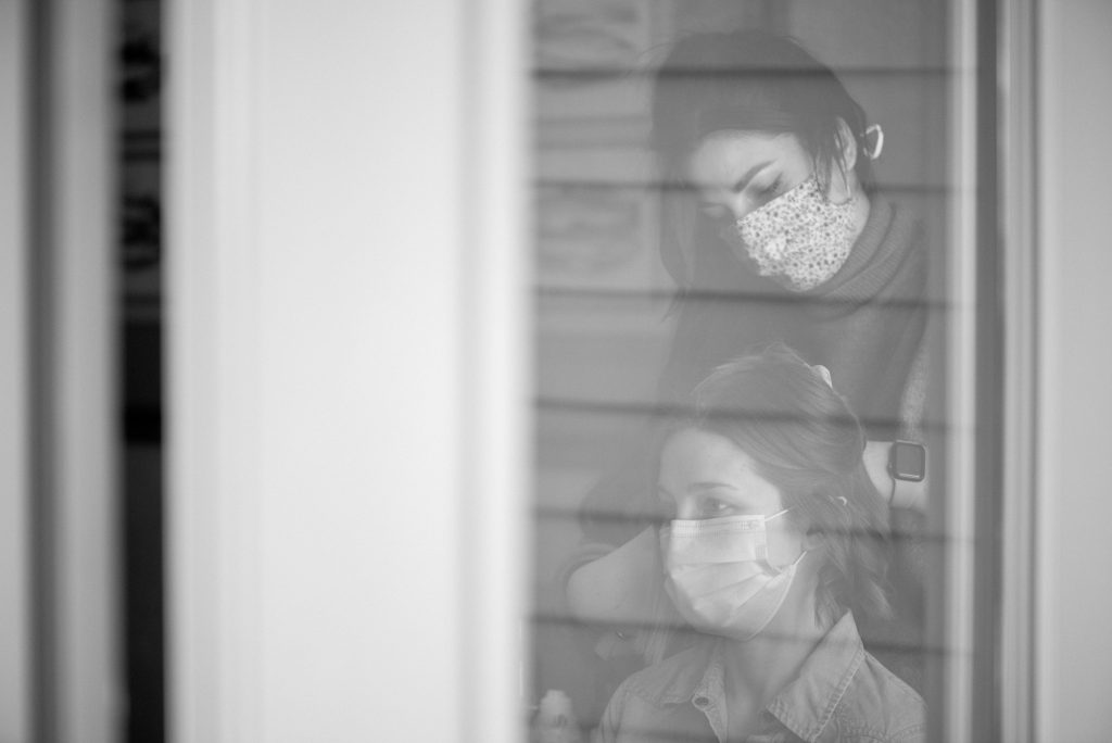 Bride wearing a face mask has her hair done on the morning of her elopement at Jasper Park Lodge