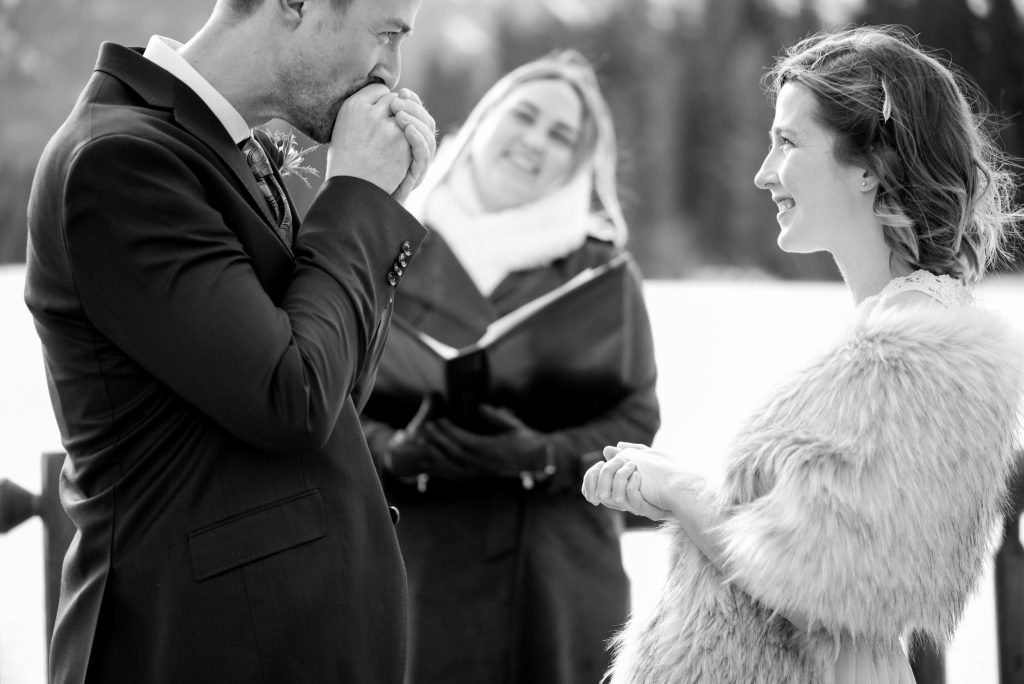 Groom warms up the rings during his intimate winter elopement ceremony in Jasper National Park