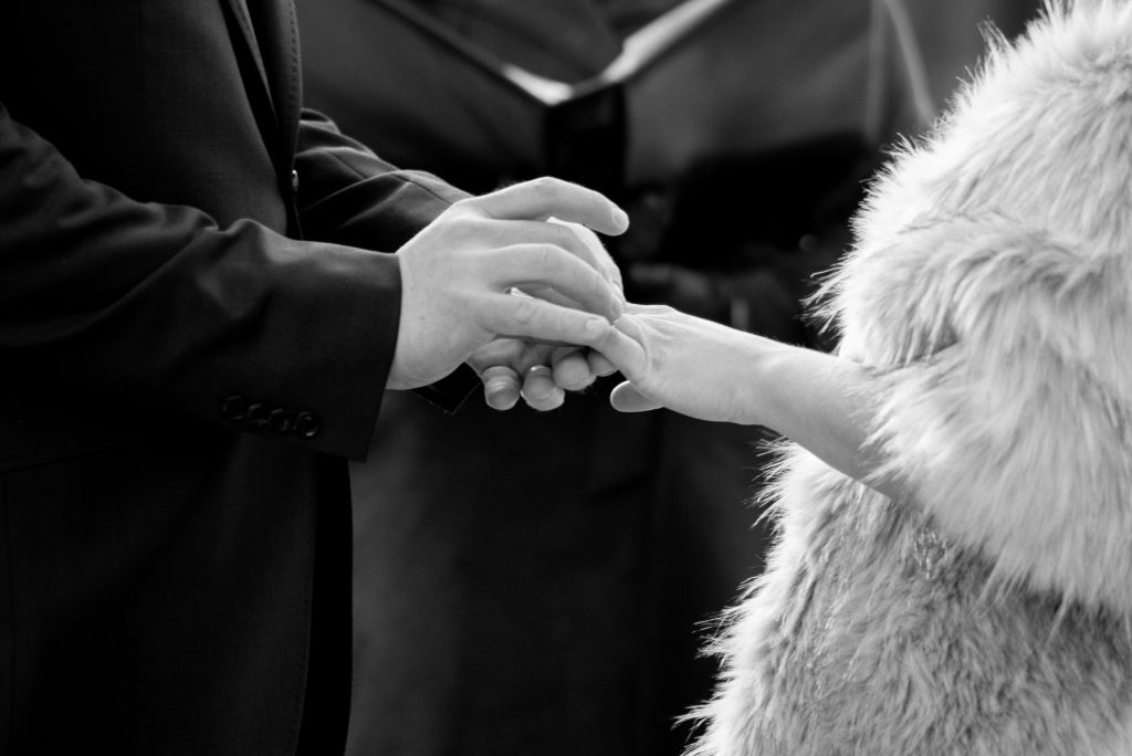 Groom places wedding band on his bride's finger