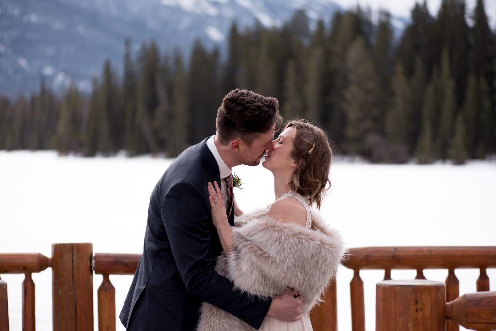 Eloping winter bride and groom share their first kiss in Jasper National Park
