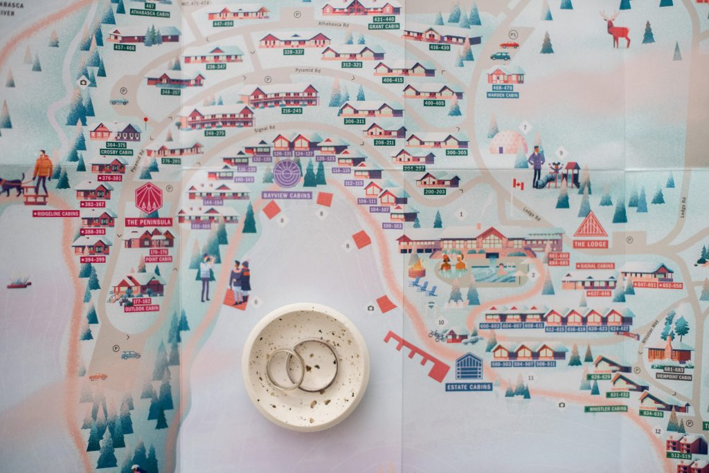 Set of wedding rings photographed on top of a playful and colourful map of the Fairmont Jasper Park Lodge