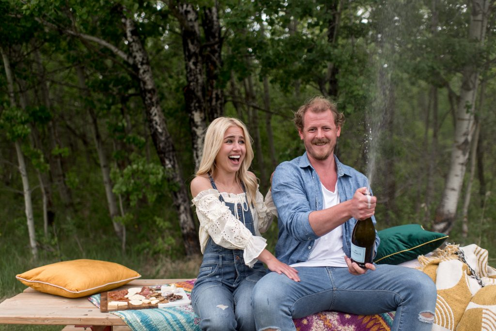 Colourful summer picnic engagement session with champagne poppin'