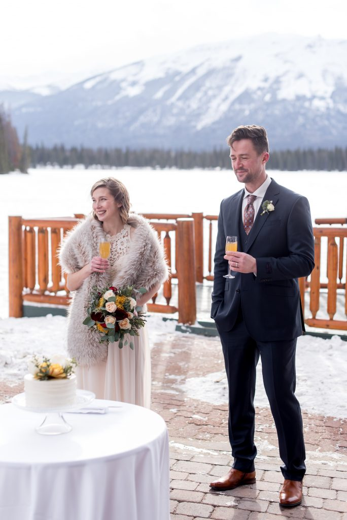 Bride and groom share mimosas at the Fairmont Jasper Park Lodge after their winter mountain elopement