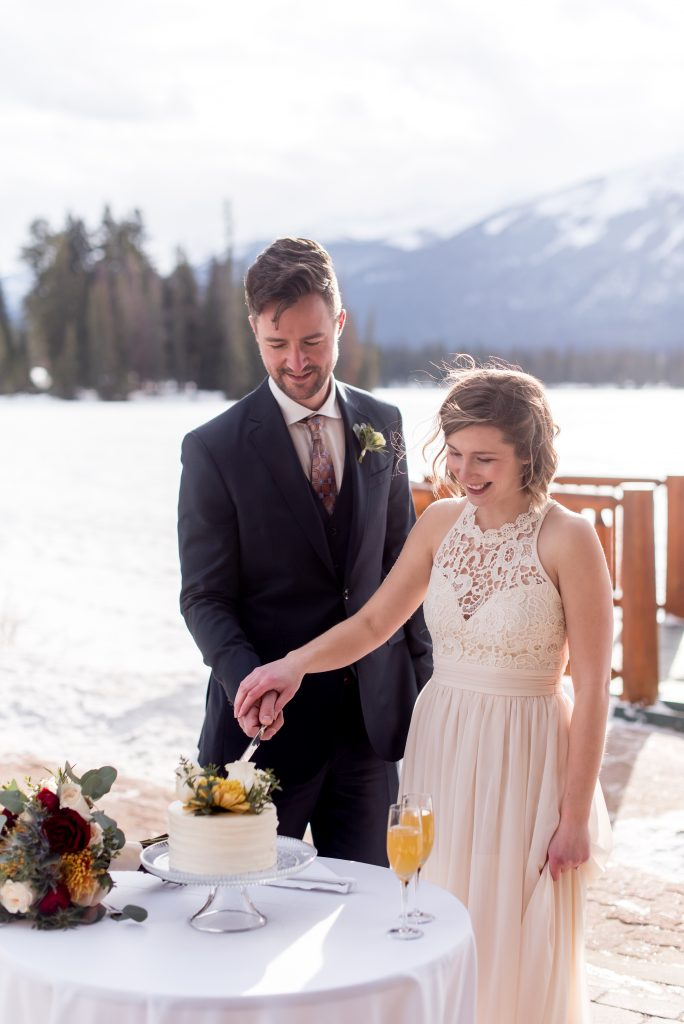 Bride and groom cut their cake after their intimate elopement ceremony at Jasper Park Lodge