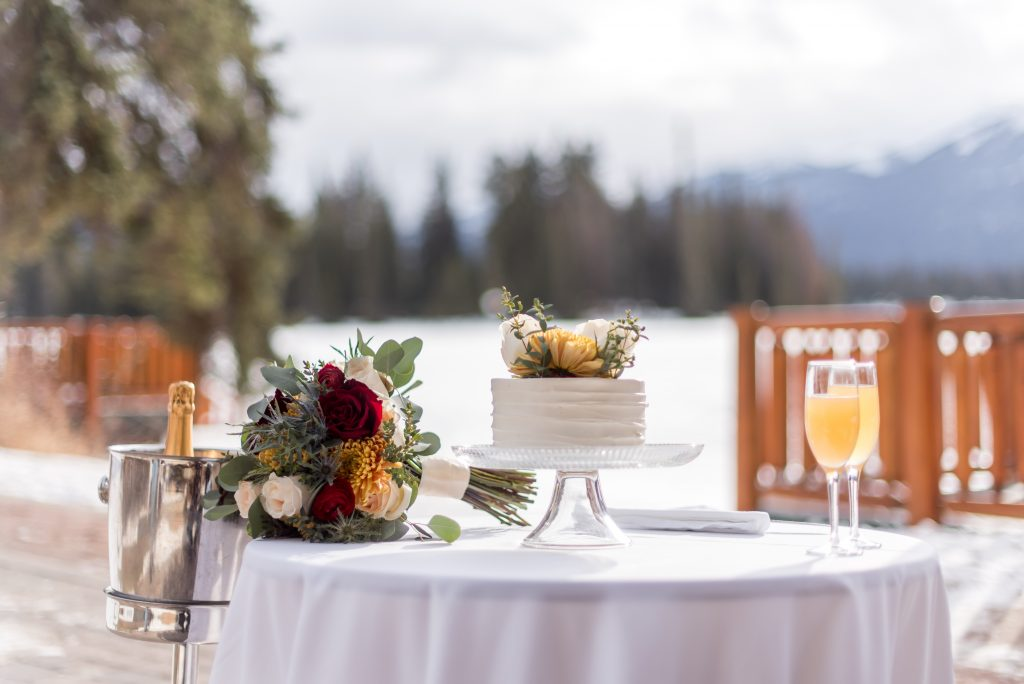 Intimate elopement package for a winter elopement at the Fairmont Jasper National Park with champagne, a bridal bouquet and stunning cake
