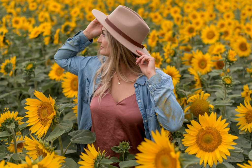 Boho chic woman poses in a field of sunflowers